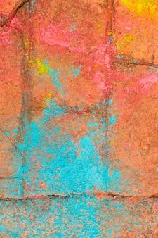 Polvo multicolor del festival holi en la acera de ladrillo rojo.