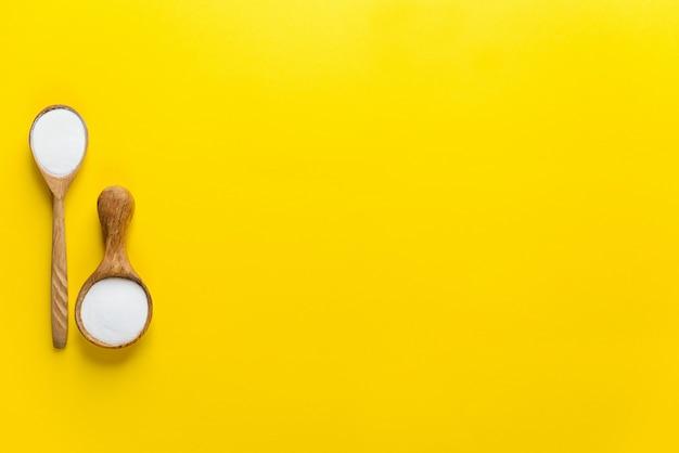 Polvo de péptidos de colágeno en cucharas de madera sobre un fondo amarillo. suplemento dietético.