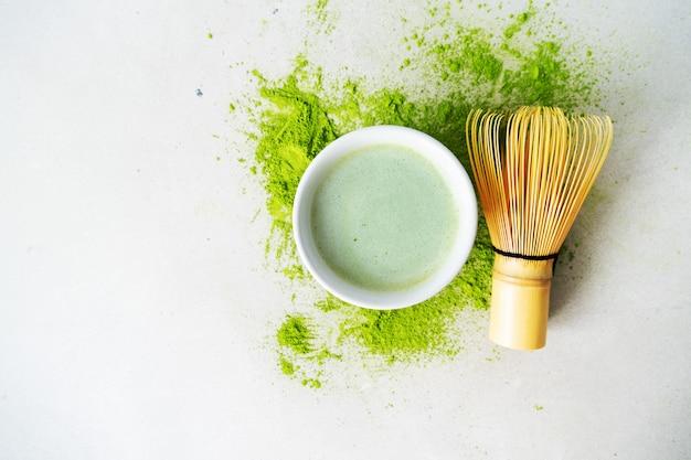 Polvo plano de té verde orgánico matcha en polvo con herramientas japonesas chasen batidor de bambú