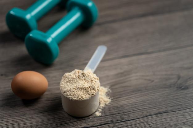 Polvo de proteína de suero en cuchara y mancuernas. bebida deportiva, nutrición para el crecimiento muscular.