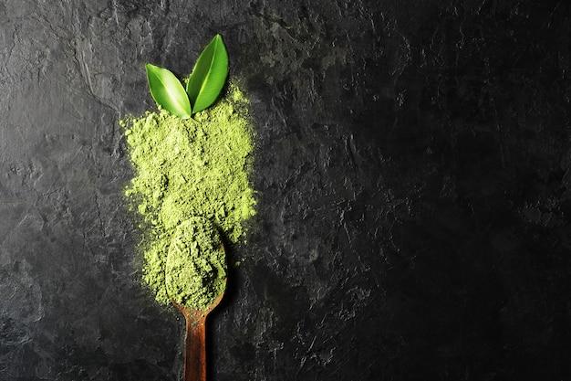 Polvo de té matcha sobre fondo oscuro con cuchara y hojas con espacio de copia.