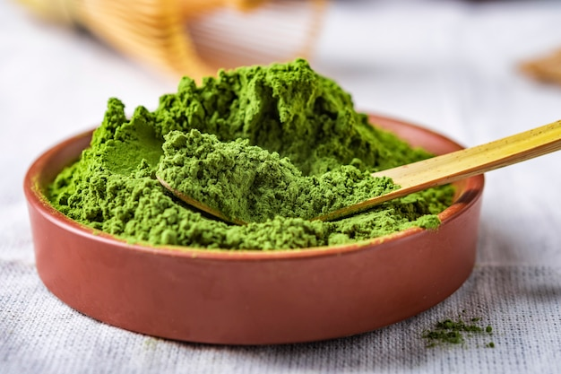 Polvo de té verde con hoja en plato de cerámica sobre la mesa, batidor de alambre japonés hecho de bambú para la ceremonia del té de macha
