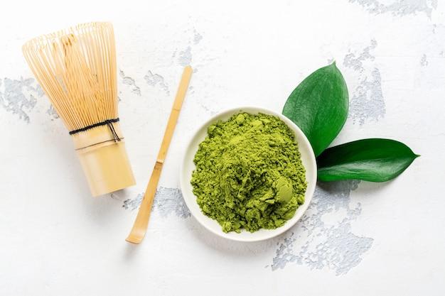 Polvo verde del té del matcha y accesorios del té en el fondo blanco