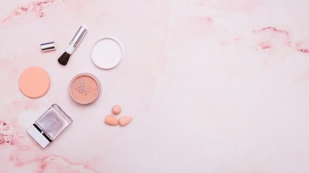 Polvos para la cara; brocha de maquillaje; borla para empolvarse; botella y licuadora sobre fondo rosa