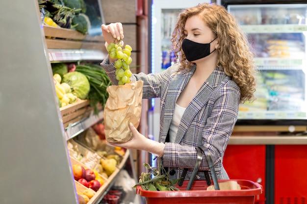 Poman con máscara en el mercado de compras