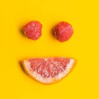 Pomelo y frambuesas en forma de sonrisa.