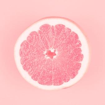 Pomelo jugoso fresco partido en dos rosa en fondo rosado
