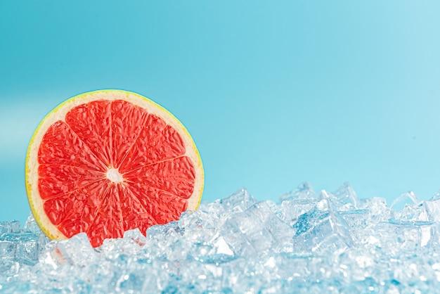 Pomelo maduro en rodajas sobre hielo