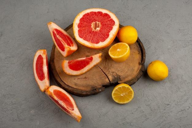 Pomelo en rodajas de limón agrio jugoso en el escritorio de madera marrón y gris