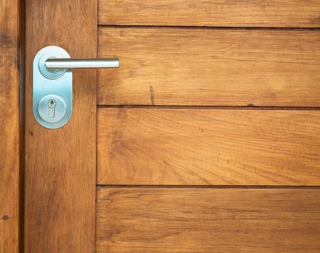 Pomo de puerta de metal en puerta de madera de teca real