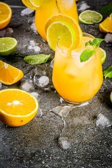Ponche cítrico con naranjas y lima, con ramitas de menta, refrigerado con hielo
