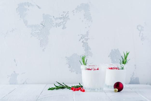 Ponche de coco navideño con semillas de granada y ramitas de romero sobre superficie clara