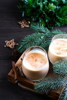 Ponche de huevo christmas cocktail de leche con canela, servido en dos vasos en bandeja vintage con rama de abeto en madera oscura