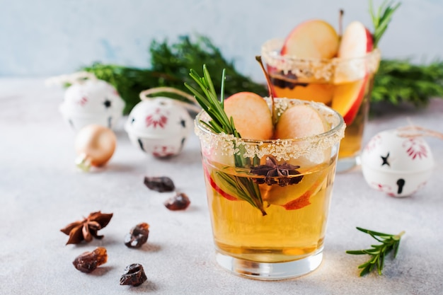 Ponche de manzana tradicional de navidad con canela, anís y ramitas de romero sobre fondo claro