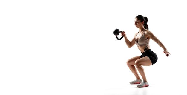 Se pone en cuclillas con peso. entrenamiento de la atleta femenina profesional caucásica aislada en la pared blanca. mujer musculosa y deportiva. concepto de acción, movimiento, juventud, estilo de vida saludable. copyspace para anuncio.