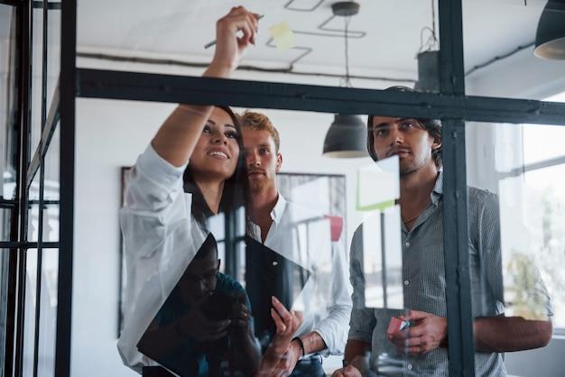 Pone pegatinas en el cristal. jóvenes empresarios en ropa formal que trabajan en la oficina.
