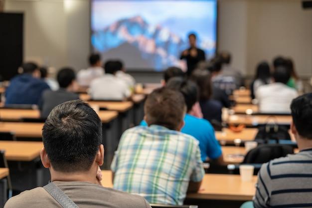 Ponente en el escenario frente a la sala con vista posterior de la audiencia en acción puesta