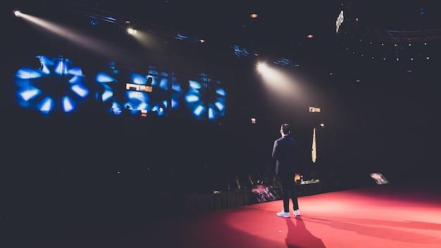 Ponente en el escenario en una sala de conferencias.