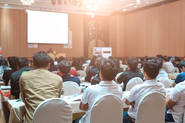 Ponentes en el escenario con vista posterior de la audiencia en la sala de conferencias o en la reunión del seminario
