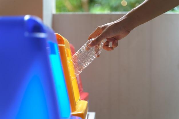 Poner la botella a mano para reciclar la papelera
