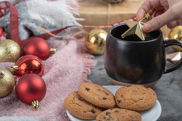 Poner una estrella dorada de navidad en una taza de bebida