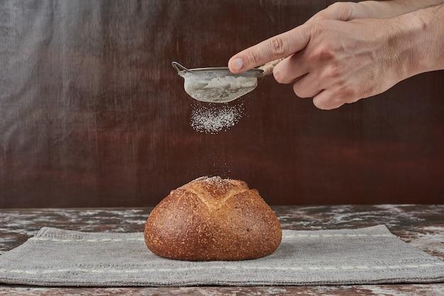 Poner harina encima de un bollo de pan.
