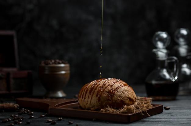Poner jarabe de chocolate en un producto de panadería dulce