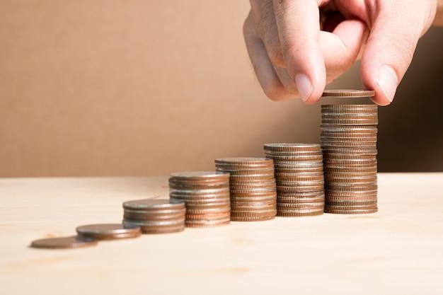 Poner a mano monedas apiladas para ahorrar en el futuro y financiar la inversión del valor de las acciones.
