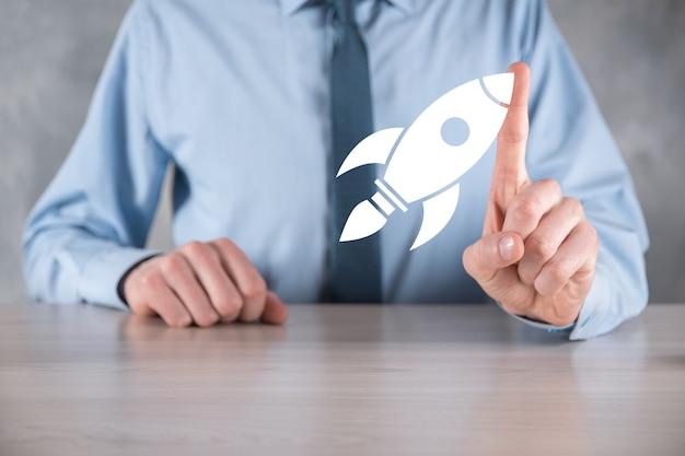 Poner en marcha el concepto con el empresario sosteniendo el icono de cohete digital abstracto el cohete se está lanzando y se eleva volando.