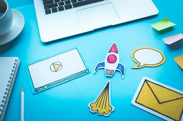 Poner en marcha conceptos con cohete y símbolo digital en la mesa de escritorio azul