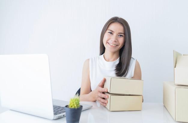 Poner en marcha un pequeño empresario empresarial pyme o una mujer independiente con cajas trabajando en casa concepto