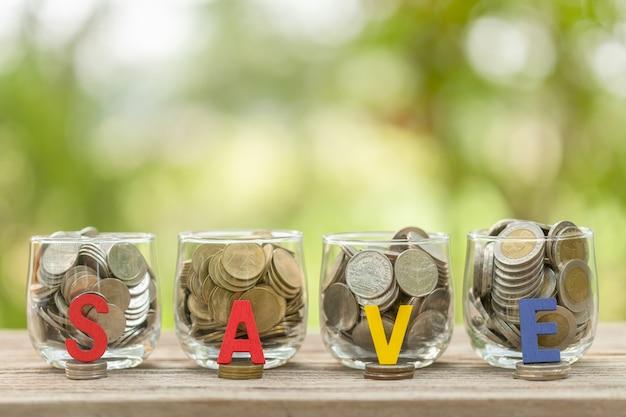 Poner monedas a mano en un frasco de dinero claro en la mesa de madera con luz verde borrosa concepto de ahorro