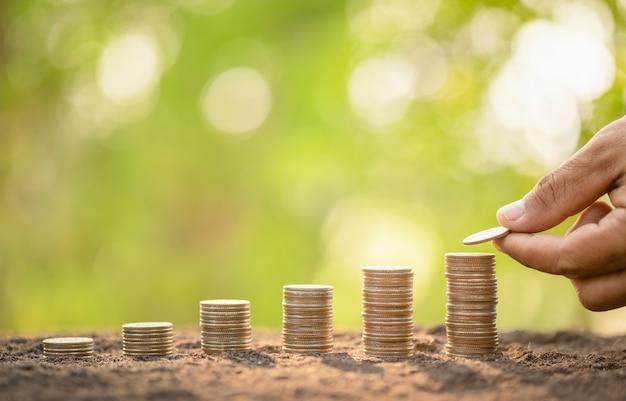Dé poner monedas en pila en tablón de madera con el fondo verde de la falta de definición. concepto de dinero, finanzas o ahorro