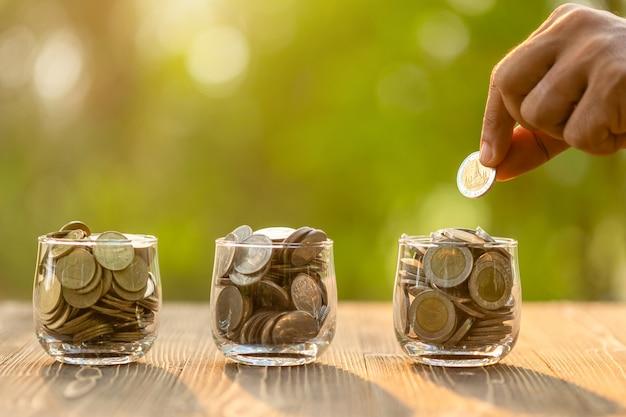 Dé poner monedas en el tarro claro del dinero en la tabla de madera con el fondo verde de la falta de definición clara. concepto de ahorro