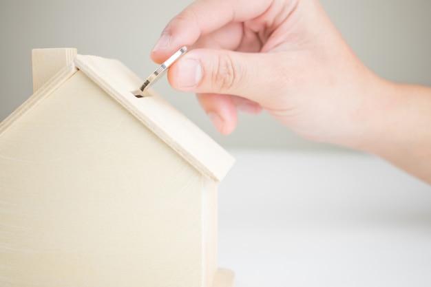 Ponga dinero en una caja modelo de una casa de madera.