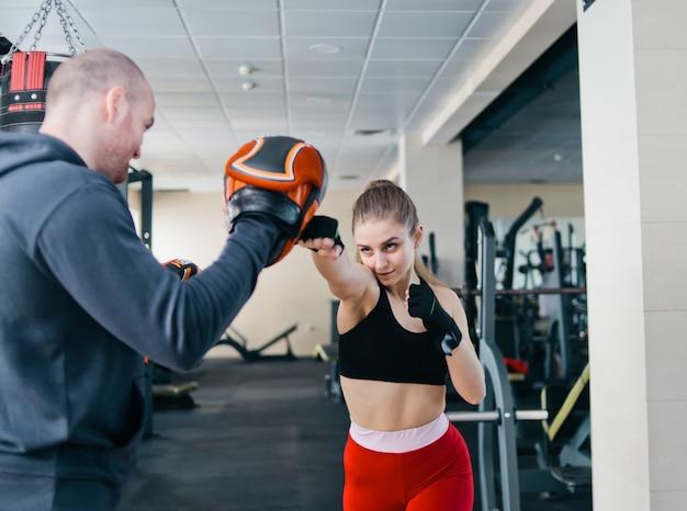 Ponga el golpe de entrenamiento de mujer rubia con entrenador de hombre. en el gimnasio. par hacer ejercicio de perforación