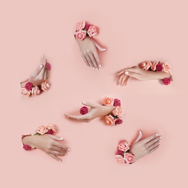 Ponga las manos con flores artificiales que sobresalen de la superficie de papel rosa. entregue varias poses, el diseño del patrón para su collage. cosméticos para el cuidado de la piel de las manos, hidratantes