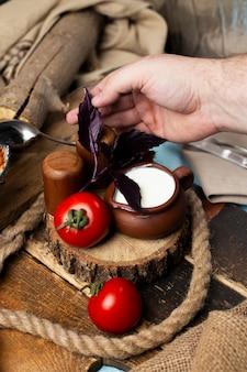 Poniendo tomates, yogur y hojas rojas de albahaca juntas.