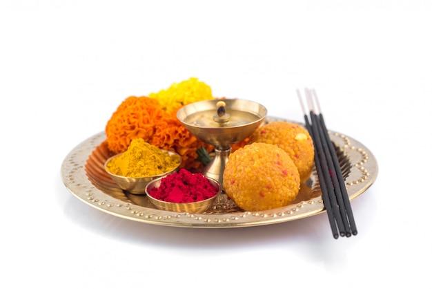 Pooja thali bellamente decorada para la celebración del festival de adoración, polvo de haldi o cúrcuma y kumkum, flores, palos perfumados en placa de latón, puja thali hindú