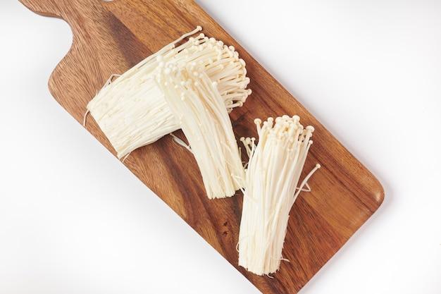 Popular en la cocina asiática, seta de aguja dorada fresca o enoki, enokitake en tabla de cortar de madera. vista superior. endecha plana. recién salido del huerto orgánico de crecimiento doméstico. concepto de comida.