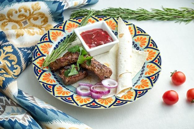 Porción apetitosa brocheta de ternera, servida con pan de pita, cebolla y salsa roja en un plato estampado sobre un mantel blanco. parilla