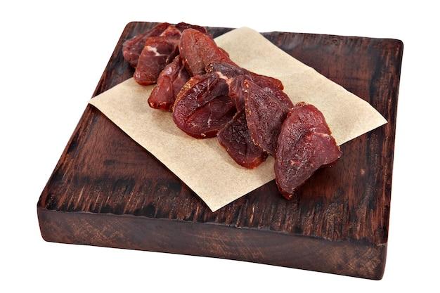 Porción de carne seca en pergamino y rojo oscuro de la tabla de servir trozos de carne aislados sobre fondo blanco.