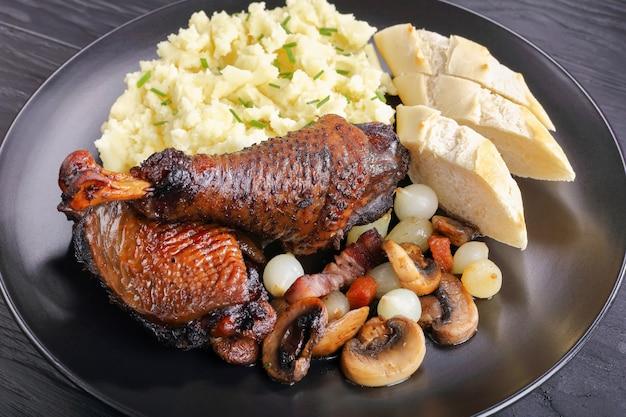 Una porción de coq au vin con estofado de pollo servido con puré de papa