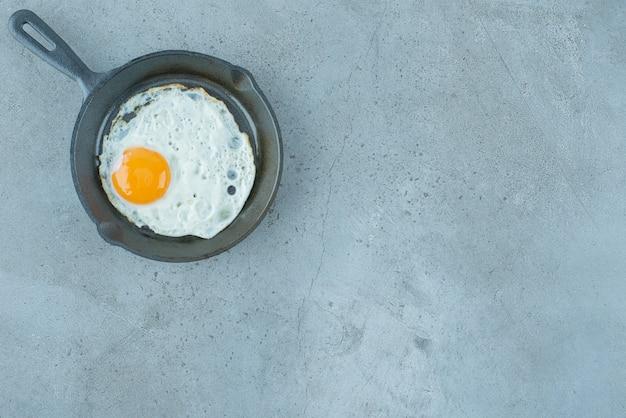 Una porción de huevo frito en una sartén sobre fondo de mármol. foto de alta calidad