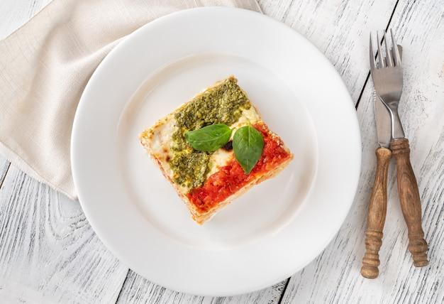 Porción de lasaña cubierta con salsa de tomate y pesto