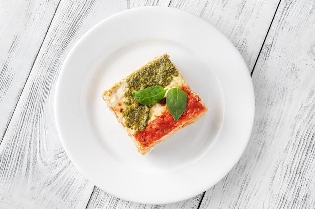 Porción de lasaña de ricotta cubierta con salsa de tomate y pesto