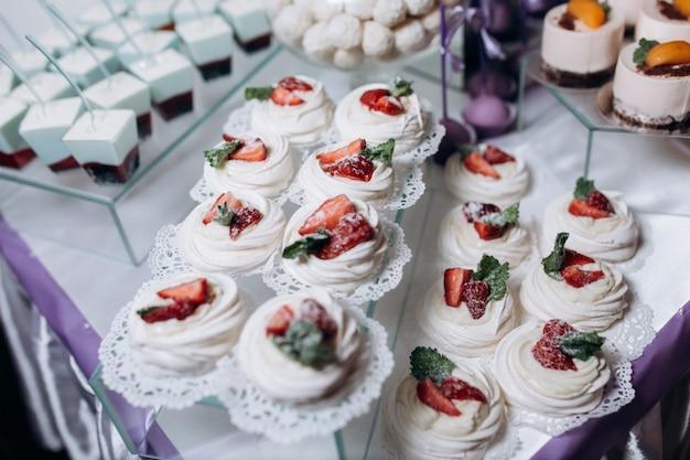Porción de merengues decorados con menta y fresa servidos en mesa de catering