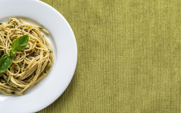 Porción de pasta con salsa de pesto y hojas de albahaca