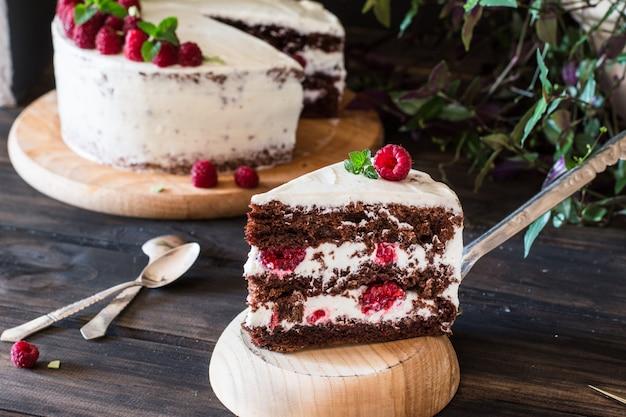Porción de pastel de frutas cremoso en capas. tarta de frambuesa. pastel de chocolate. tarta de queso. negro fo