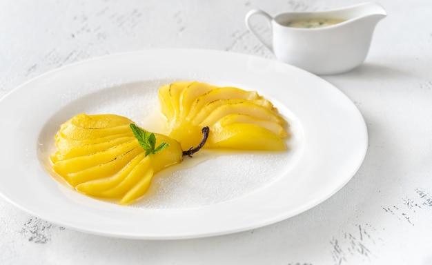 Porción de peras escalfadas con azafrán en la placa blanca.
